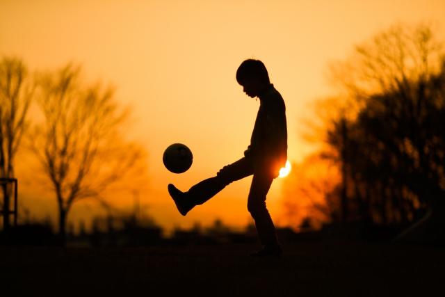 サッカーする子ども 夕日